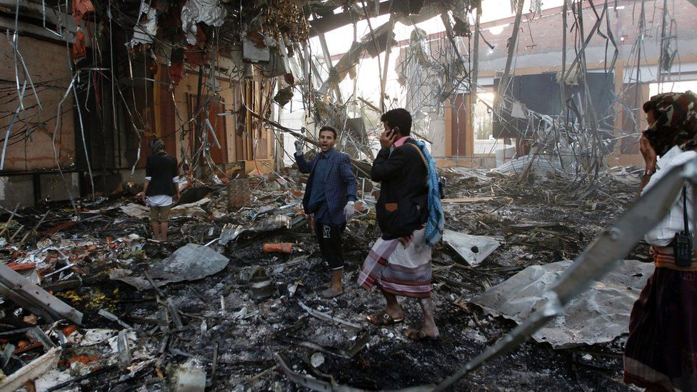 Yemeni rescue workers search for victims amid the rubble of a destroyed building following reported airstrikes by Saudi-led coalition air-planes on the capital Sanaa on October 8, 201