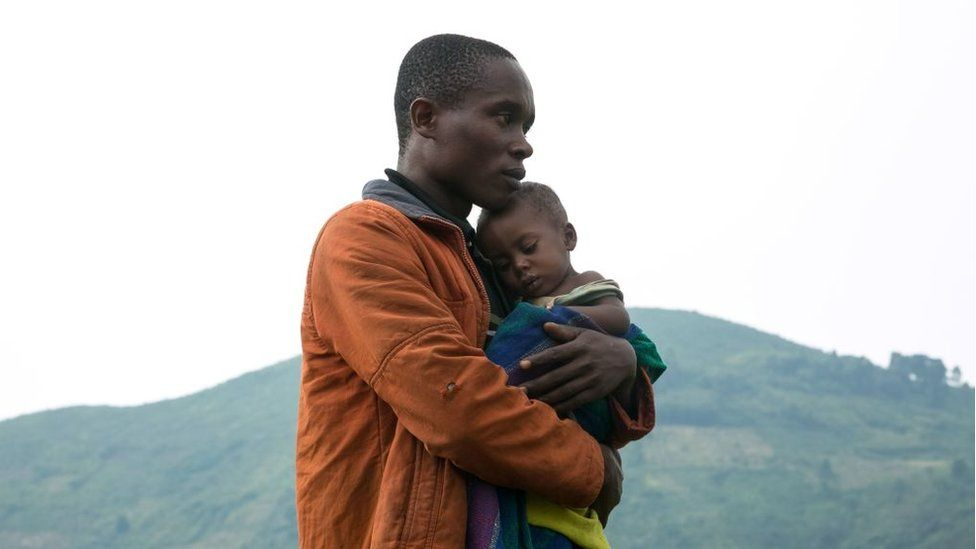 A Congolese man holds his child after he crossed the border from the Democratic Republic of Congo (DRC) to be refugees at Nteko village in western Uganda on January 24, 2018.
