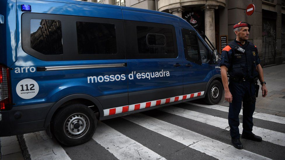 Officer of the Catalan police force stands by a squad van in Barcelona.