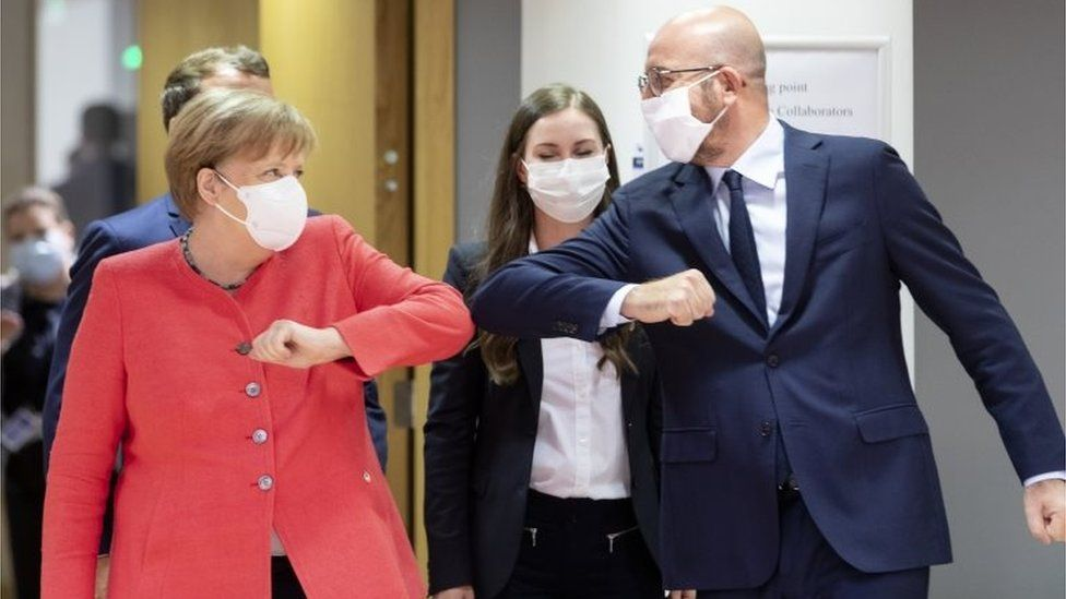 German Chancellor Angela Merkel (L) elbow bumps the President of the European Council Charles Michel (R) during an EU summit on July 17, 2020 in Brussels, Belgium.