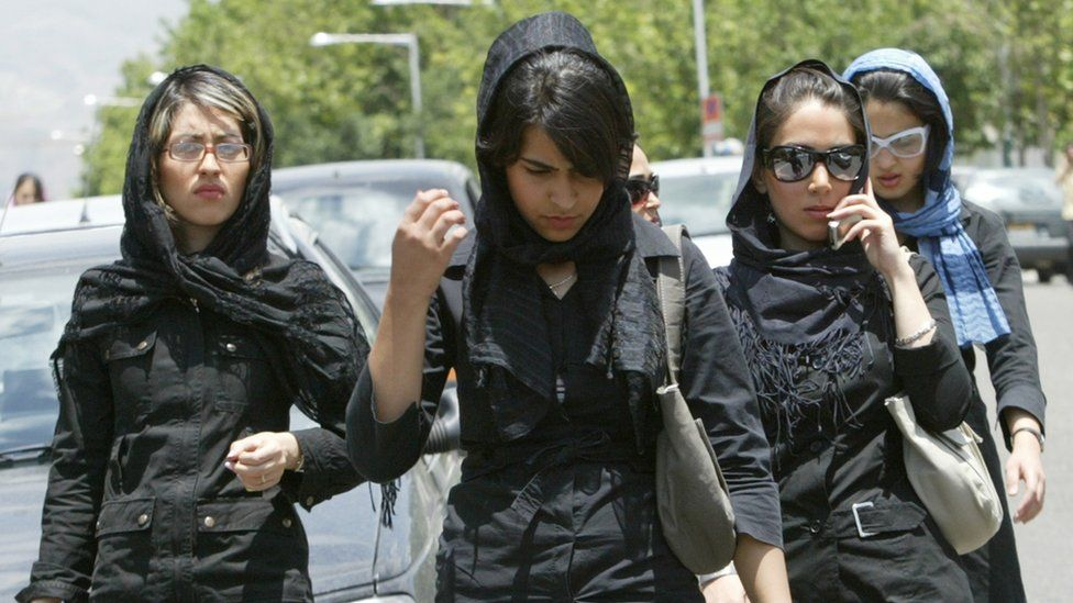 Iranian women in veils walk outside a shopping centre in Tehran on 2 June 2005