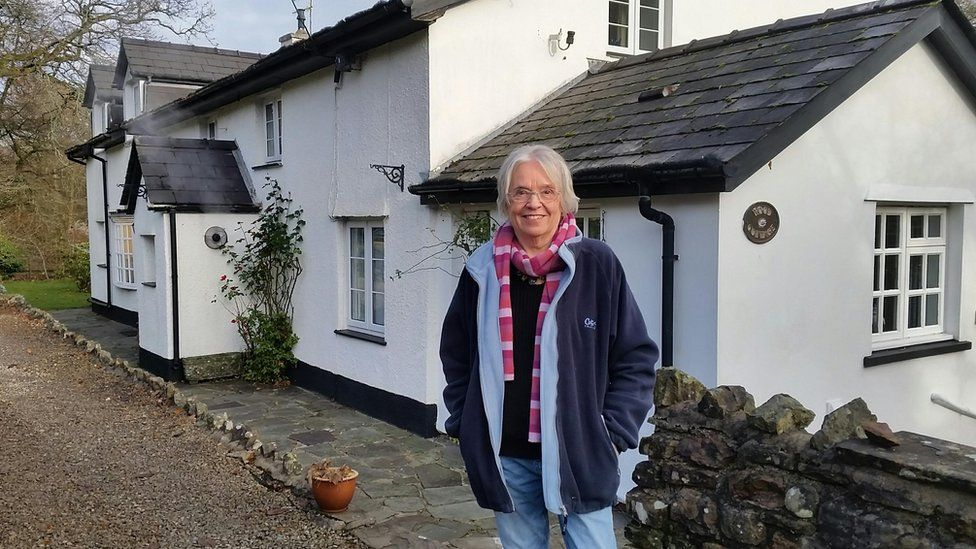 Norma Procter in front of house