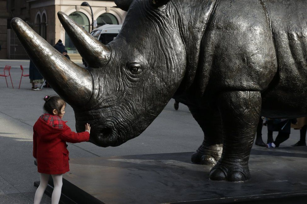 A young child touches The Last Three, the world's largest rhino sculpture, which is on display by artists Gillie and Marc Art at Astor Place in New York, New York, USA, 15 March 2018