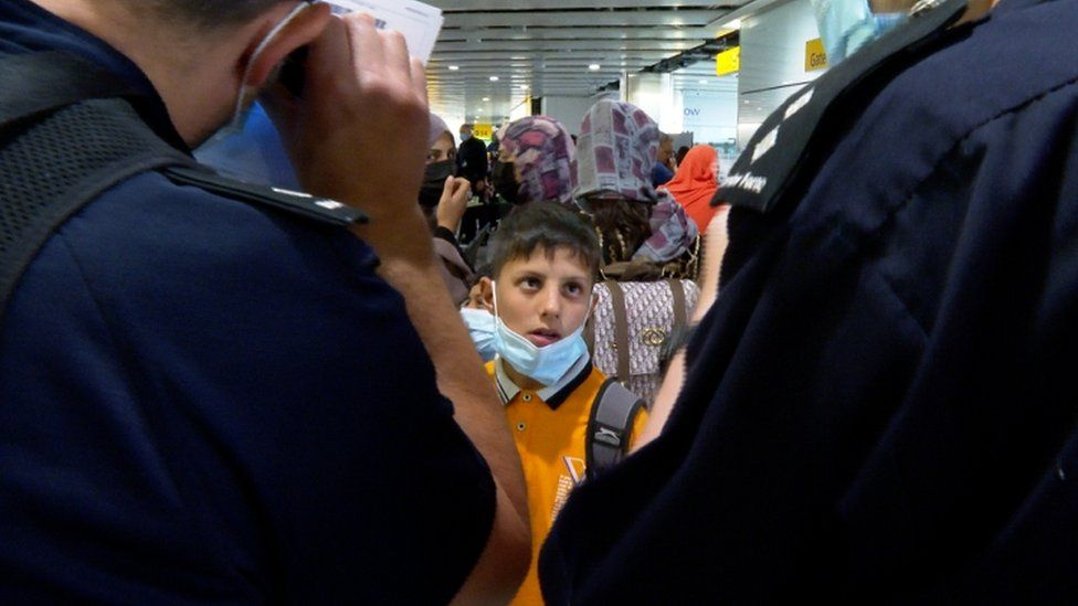 A boy looks on at border force officers