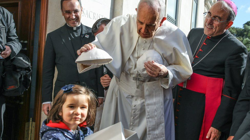 Pope Francis, accompanied by Leiria-Fatima Bishop Antonio Marto (right), changes skull-caps with a young child at the entrance of the Our Lady Rosario Cathedral at the Fatima Sanctuary, in Leiria, Portugal, 13 May 2017