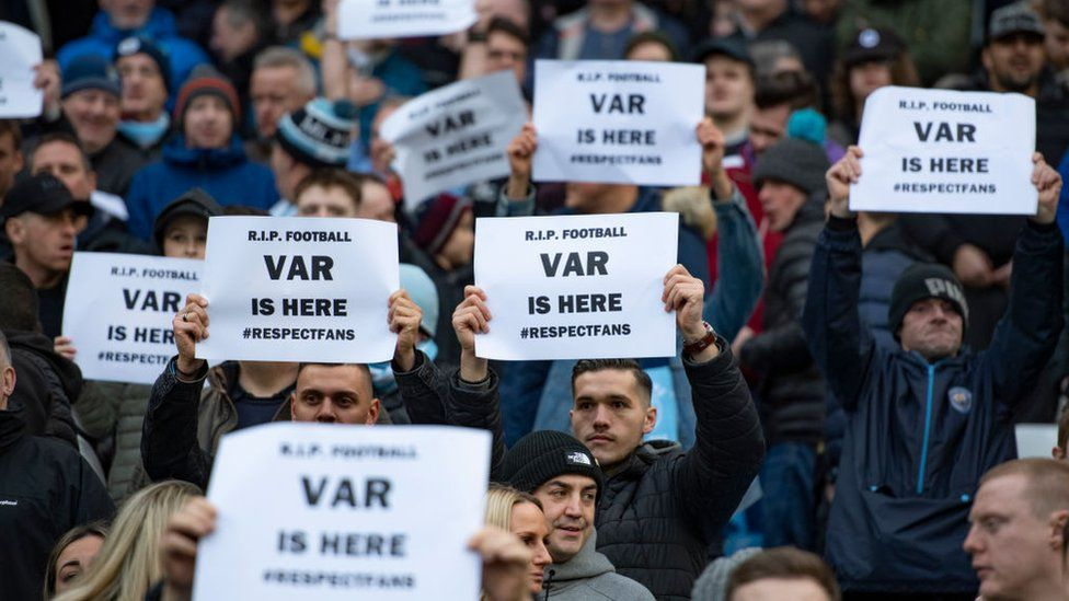 """Fans hold up signs saying """"VAR is here"""""""
