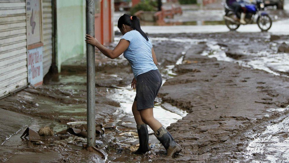 A woman walks in a mud after the hurricane Otto came through Upala, San Carlos, Costa Rica