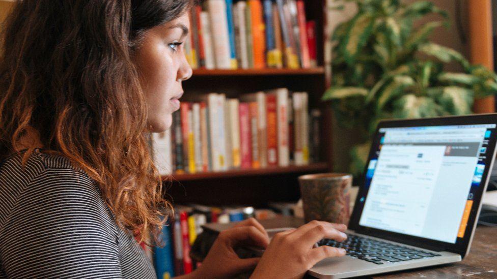 A woman taping at a computer