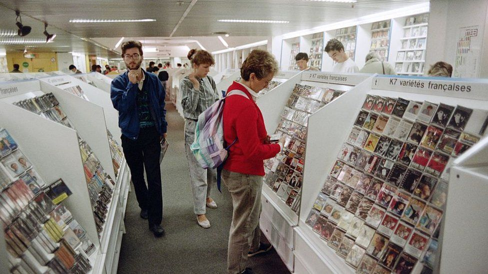 Customers look at music cassettes displayed at a Fnac store, on August 28, 1987