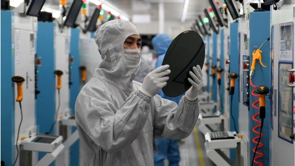 Employees work on the production line of silicon wafer at a factory of GalaxyCore Inc. on May 25, 2021 in Jiashan County, Jiaxing City, Zhejiang Province of China