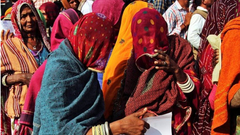 Women check their documents as they queue outside a bank to exchange and deposit their old high denomination banknotes in Gagwana village in the desert Indian state of Rajasthan