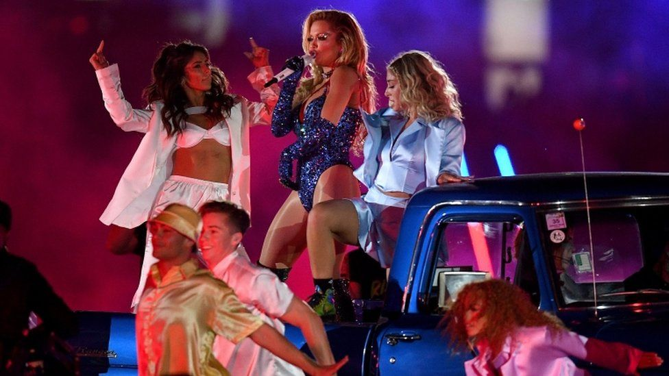 Rita Ora performs with dancers on a truck during the parade event