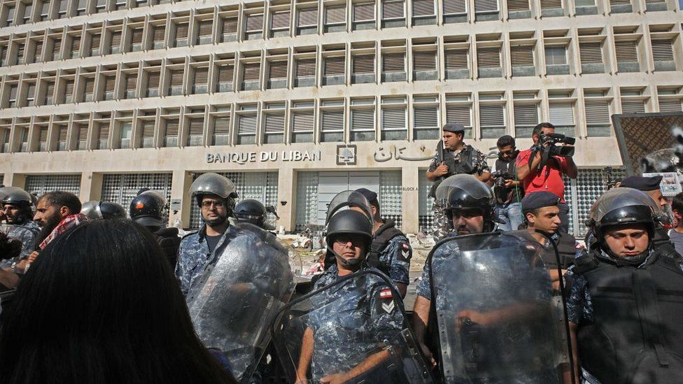 Lebanese security forces secure the entrance of the Central Bank after anti-government protesters broke down a construction barrier as they rally at the same time of a press conference held by the bank's governor in Beirut on November 11, 2019.