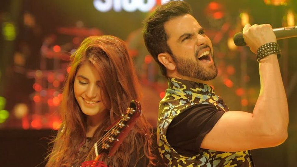 Momina Mustehsan plays guitar next to a male singer on the Coke Studio show