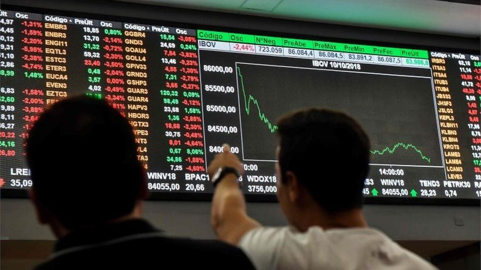 People look at an electronic board at the Sao Paulo Stock Exchange on October 10, 2018