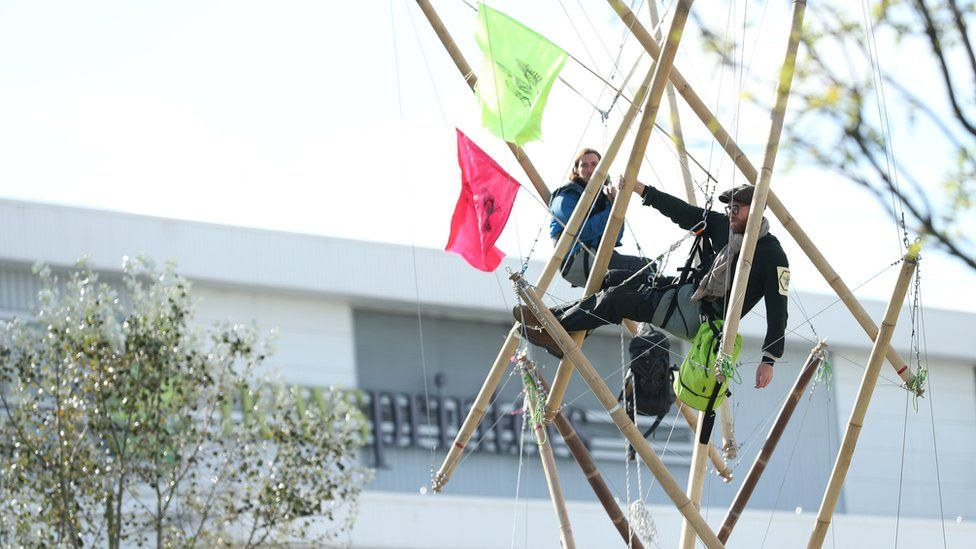 Protesters chained to bamboo structures outside the presses in Hertfordshire