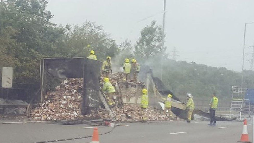 Firefighters remove chocolate cargo to clear the carriageway
