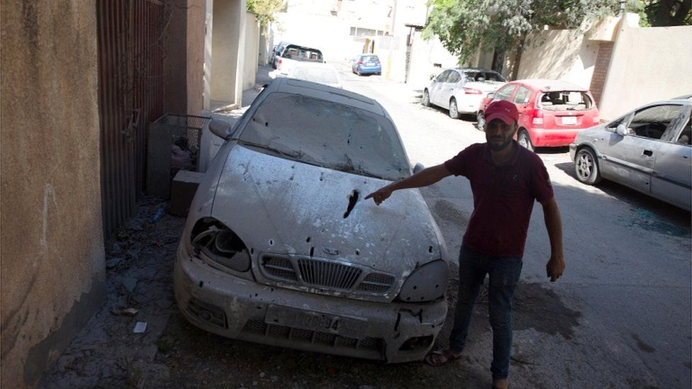 A man looks at a damaged car after rockets fired by unknown militants landed on the residential area of Ben Ashour, Tripoli, on 1 September 2018
