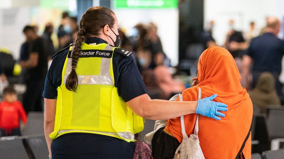 A member of Border Force staff assisting an Afghan refugee on her arrival on an evacuation flight from Afghanistan