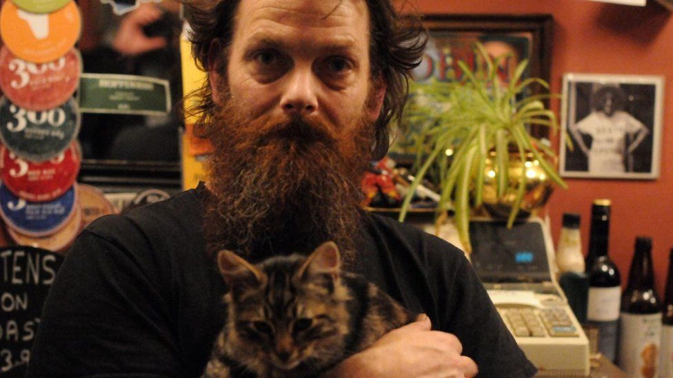 Landlord Luke Daniels with a cat in the Bag of Nails Pub in Bristol
