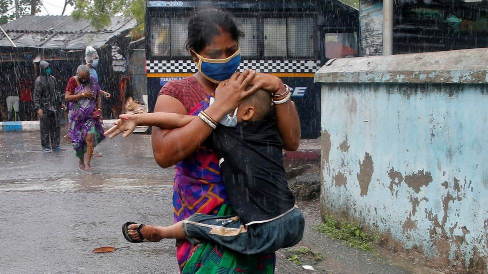 A woman carries her son as she tries to protect him from heavy rain while they rush to a safer place, following their evacuation from a slum area before Cyclone Amphan makes its landfall, in Kolkata