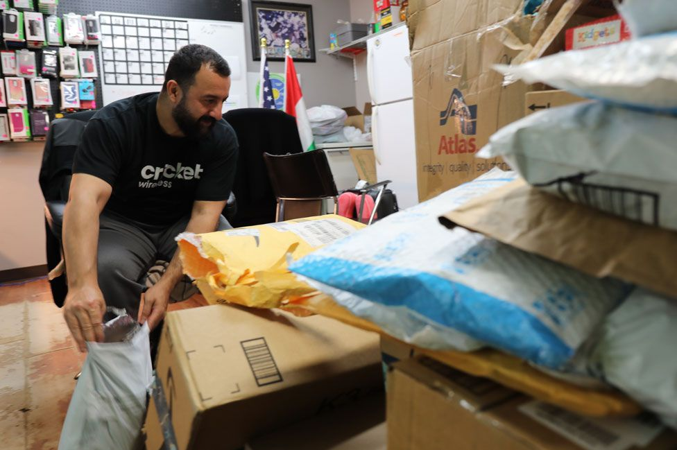 Nejeer Zebari sifts through a new arrival of boxed donations
