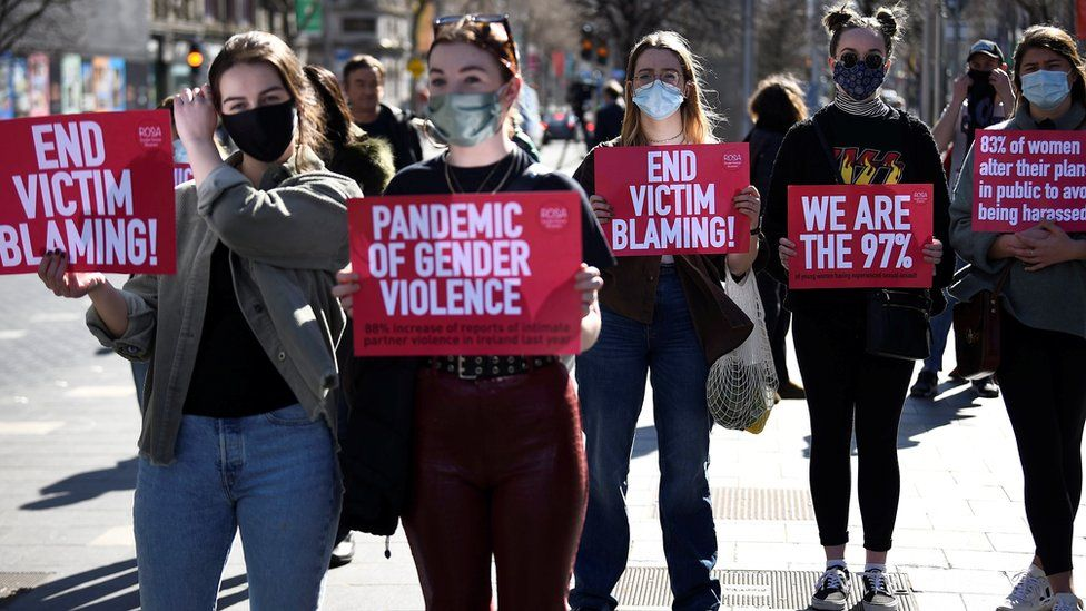 Women display signs to protest against violence