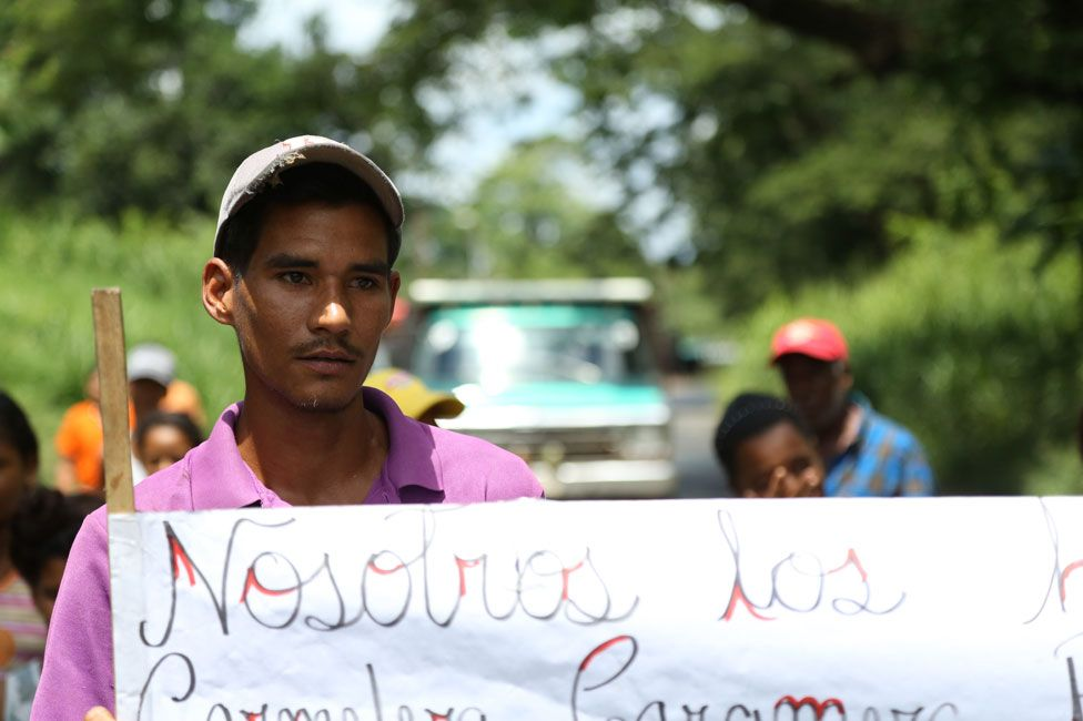 Young man at the roadblock erected by people who have been surviving on mangoes alone