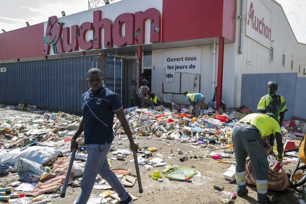 Shop owners clean their shops damaged by protesters during demonstrations after Senegal's opposition leader Ousmane Sonko was taken into custody after court hearing, on March 06, 2021 in Dakar, Senegal.