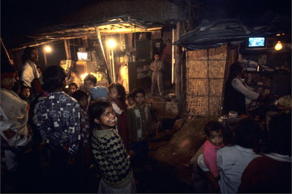 People in the streets gather around shops with televisions at night in January of 1999 in the slums of New Delhi, India.