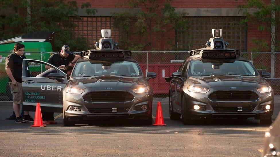 Uber driverless cars and crew members