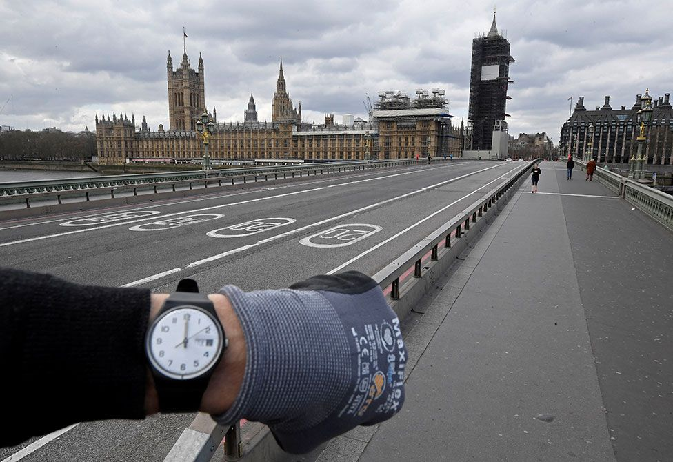 A photographer wearing a watch at noon in front of the Houses of Parliament on Westminster Bridge, in London, UK