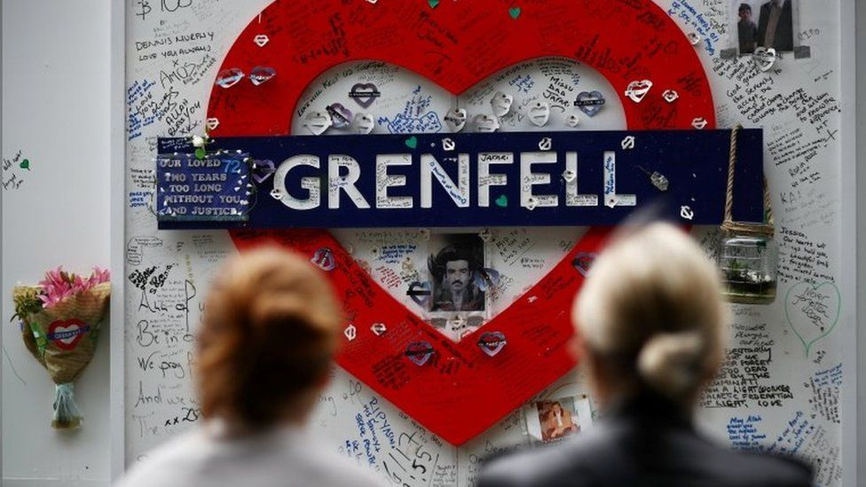A hoarding covered in messages of condolence at the base of Grenfell Tower
