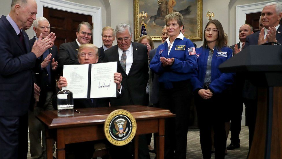 "U.S. President Donald Trump holds up ""Space Policy Directive 1"" after signing it during a ceremony."