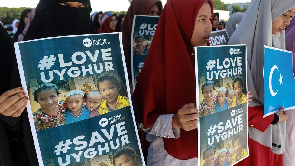 Uighur protesters in Indonesia in 2018 hold signs reading #LoveUyghur and #SaveUyghur