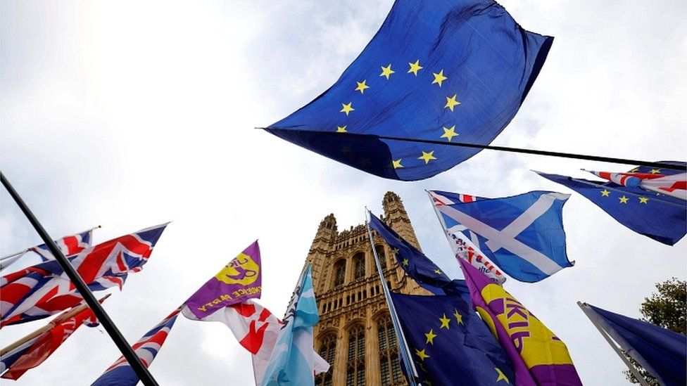 Anti-Brexit activists' EU flags are pictured alongside the Union flags of pro-Brexit activists as they demonstrate outside of the Houses of Parliament in London on 28 October 2019