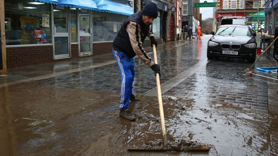 Man cleans mud from street in Pontypridd, Rhondda Cynon Taf, after Storm Dennis flooding