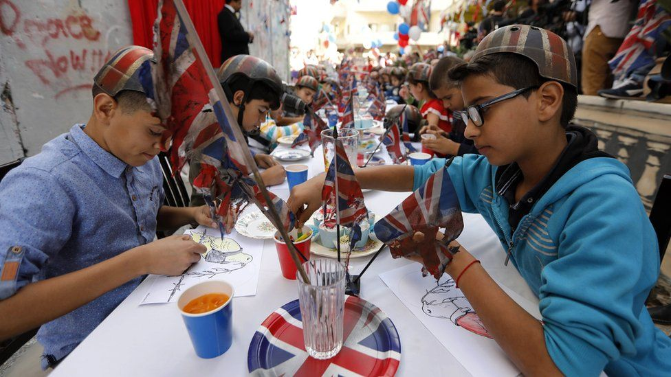 Palestinian children at a long table festooned with the British flag (1 November 2017)