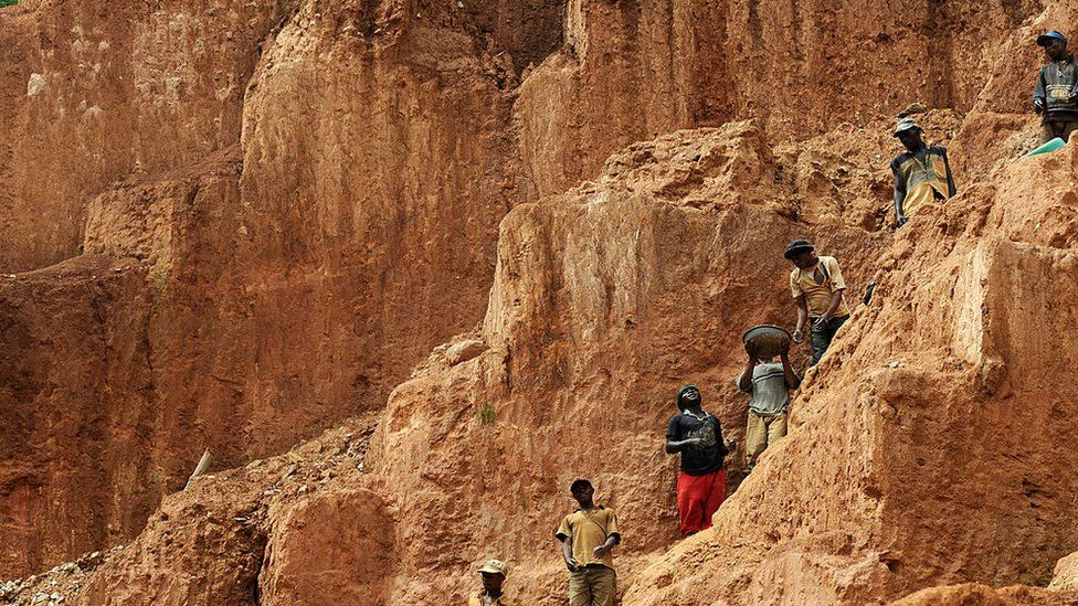 Workers stand on a muddy cliff as they work at a gold mine on February 23, 2009 in Chudja, near Bunia, north eastern Congo. The conflict in the Congo has often been linked to a struggle for control over its minerals resources. The Congo is rich in mineral resources such as gold, diamonds, tin, and cobalt