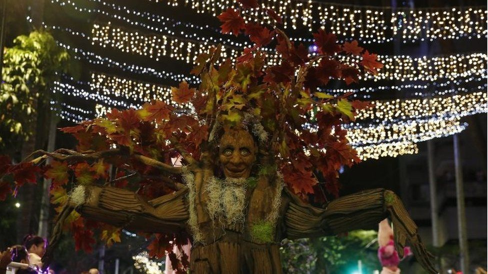 An artist dressed as a tree takes part in a parade in Medellín
