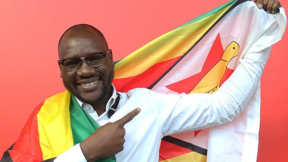 Pastor Evan Mawarire posing with a Zimbabwean flag