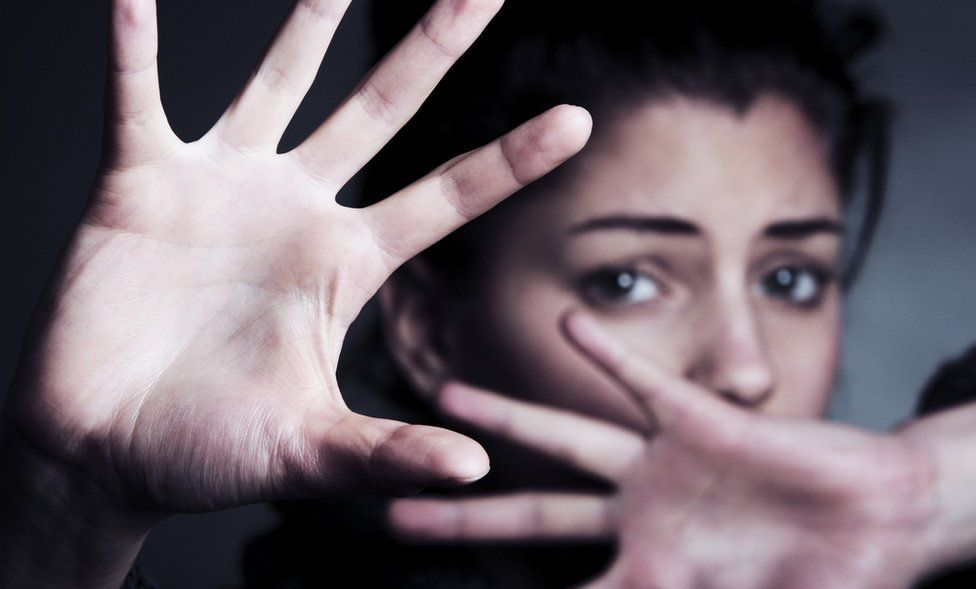 Woman shielding her face with her hands