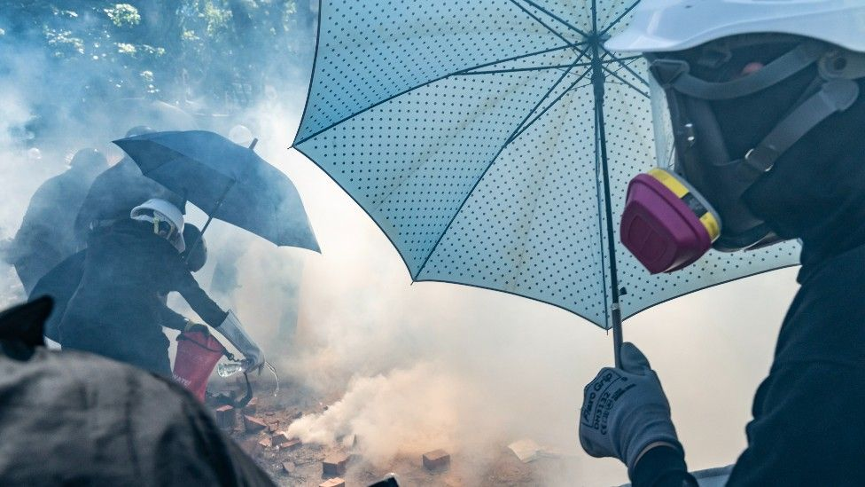 Manifestantes con paraguas y mascarillas.