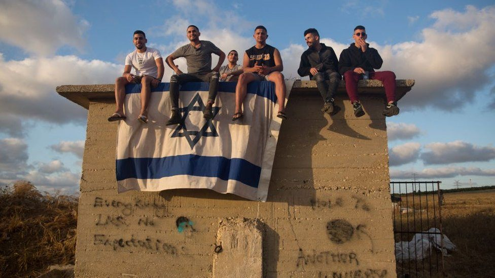 Israelis gather to watch the Iron Dome missile defence system launch to intercept rockets fire from the Gaza Strip