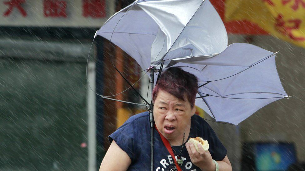 Woman eats a pork bun and struggles with her umbrella against powerful gusts of wind generated by Typhoon Megi in Taipei, Taiwan