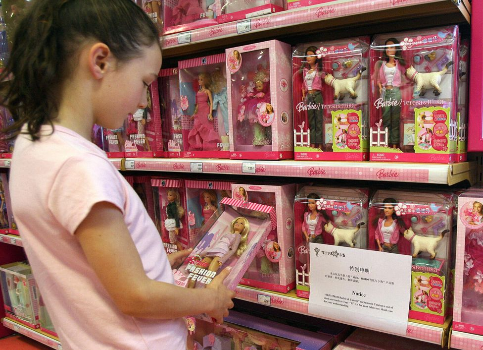 Girl looks at Barbie on toy shop shelf