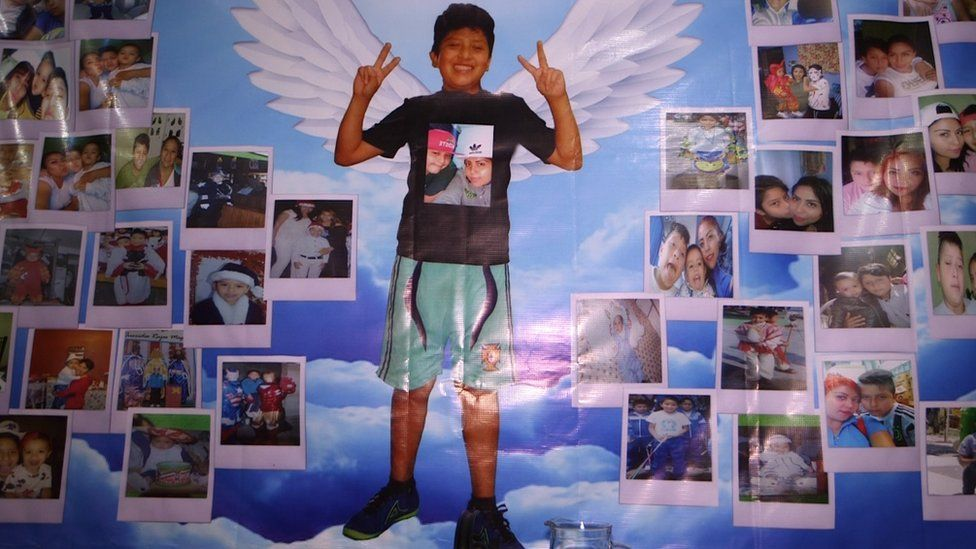 A wall hung with pictures of Brandon Giovanny at his mother's home