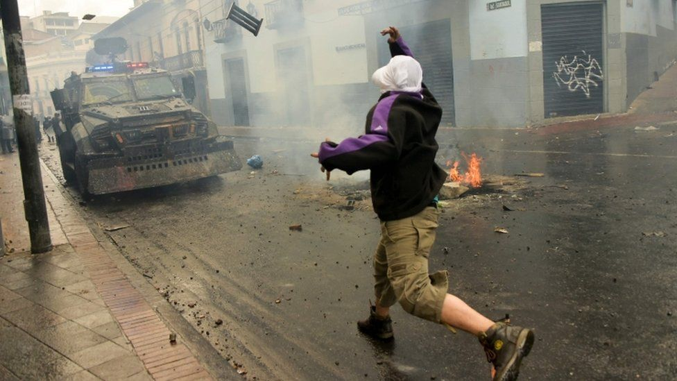A demonstrator clashes with riot police during a transport strike in Ecuador