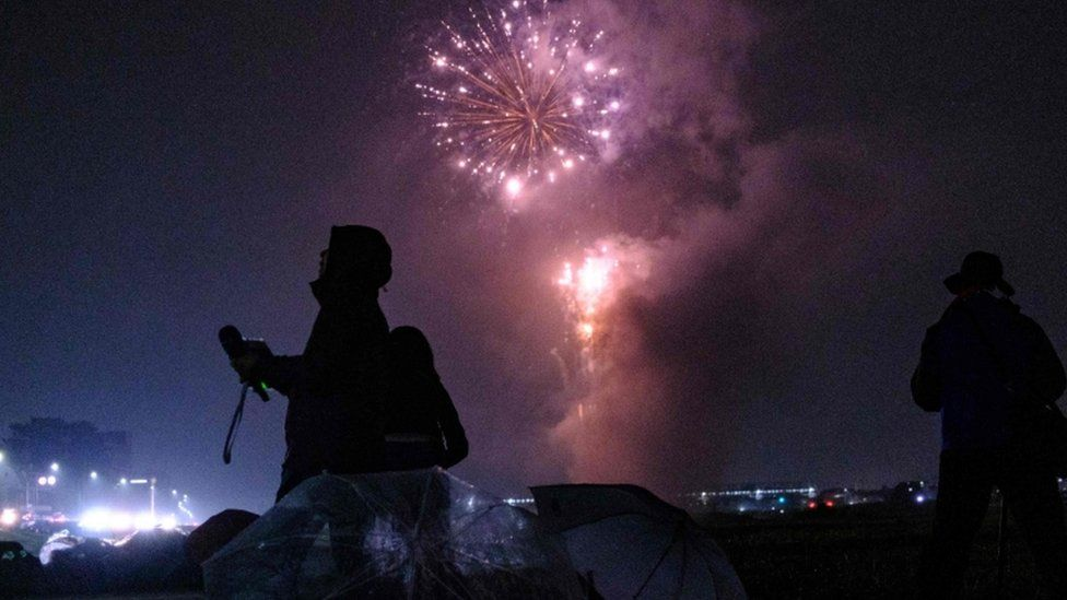 Journalists film as fireworks explode near Tama river in Tokyo