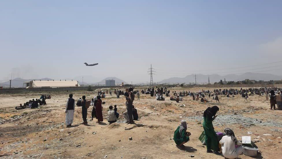 Afghans have been waiting near the airport as they try to leave Kabul